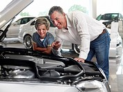 Father and son looking at car engine in automobile showroom