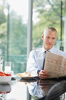 Businessman reading newspaper at breakfast table