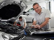 Mechanic working on engine in auto repair shop
