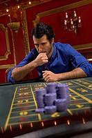 Anxious man looking at gambling chips in casino