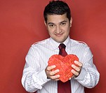 Portrait of a young man holding a heart shaped object