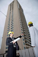 Businessmen holding blueprint gesturing at construction site,low angle view