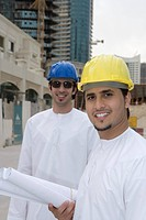Businessmen holding blueprints with buildings in background,smiling,portrait