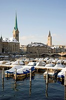 Snow-covered boats at the Limmatquai quay, in the back the Frauenmuenster church, St. Jakobs Kirche church and Muensterbruecke bridge, Zurich, Switzer...