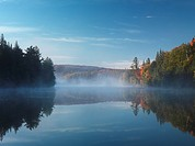 Mist over Smoke lake at dawn  Beautiful fall nature scenery  Algonquin Provincial Park, Ontario, Canada