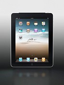 Apple iPad 3G tablet with desktop icons on its display isolated on gray background with clipping path