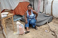Woman sitting on her bed in a tent camp for victims of the January 2010 earthquake, Delmas 89 district, Port_au_Prince, Haiti, Caribbean, Central Amer...
