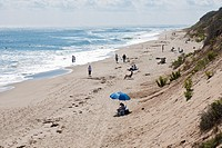Sunbathers and beach walkers on Nauset Light Beach in Eastham, Massachusetts