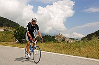 Cyclist in front of Castel del Monte, Monte Prena, Monte Camicia, Gran Sasso National Park, Abruzzo, Italy, Europe