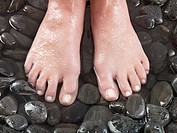 Woman's feet on pebbles
