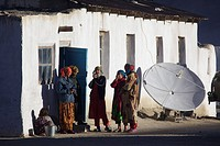 Young women in front of a home with satellite dish in Bulunkul, Pamir, Tajikistan, Central Asia
