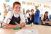 Smiling student using soldering iron in vocational school