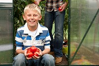 Smiling boy holding ripe tomatoes in greenhouse garden