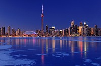 Frozen ice covered Lake Ontario reflecting the lights of Toronto city skyline at dusk