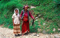An old woman in traditional dress and her granddaughter walking on a mountain path, Bhotia ethnic group, Garhwal Himalayas, India, Asia