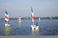 Children in sailing dinghies on outer Alster, Hamburg, Germany