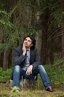 Young man sitting thoughtfully on a tree stump in a forest