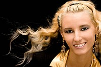 Portrait of young beautiful blond girl on black background