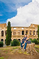 Couple posing in front of the Roman Colosseum