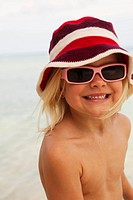Happy girl on beach wearing hat and sunglasses