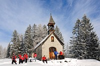 People in front of chapel on winter hiking trail in snowy landscape, Hemmersuppenalm, Reit im Winkl, Chiemgau, Bavaria, Germany, Europe