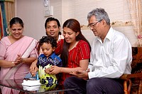 South Asian Indian small boy of 3 years cutting birthday cake MR 468
