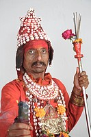 Gondhali from Sholapur District holding incense sticks and holding divti or torch, Maharashtra , India MR687X