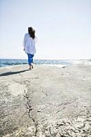 Woman walking on rock by sea
