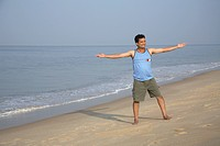 South Asian Indian young man doing aerobics on seashore , Shiroda , Dist Sindhudurga , Maharashtra , India MR703D
