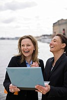 Businesswomen laughing over laptop