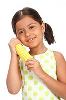 Eight year old girl holding sweet corn in both hands near her cheek MR703U