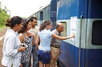 Travel group searching their names on reservation chart fixed near door of long distance train MR468