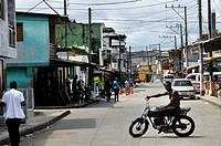 Street and a young darkskinned man on a motorcycle in the Bajamar slum, Buenaventura, Valle del Cauca, Colombia, South America