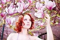Young female with red curly hair touching a magnolia flower