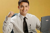 South Asian Indian businessman sitting in office with laptop raising fist MR 670I