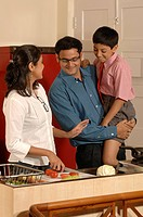 Indian working couple with son busy in well equipped kitchen in house , Bombay Mumbai , Maharashtra , India MR705W,705X,705Y