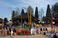 Balinese Hinduism, gathering of believers, ceremony, believers in bright temple dress, colorful flags, Balinese pagodas in the back, Pura Ulun Danu Ba...