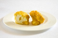 Indian cuisine , fast food starters Phoolgobi Ke Pakode crispy cauliflower puffs served in dish on white background