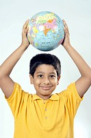 South Asian Indian boy holding globe above head and smiling MR152