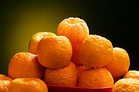 Fruit , oranges in a bowl against a yellow black background