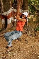 South Asian Indian teenager girl enjoying hanging on branch of banyan tree MR645