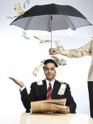 Money falling on South Asian Indian executive extend hand palm up sitting under umbrella MR702A