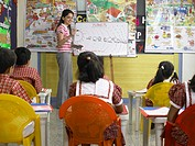 South Asian Indian teacher teaching to children in nursery school MR