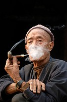 Portrait of an old man of the Mouchi ethnic group smoking a pipe, smoke covering his face, smoking for pleasure, village of Ban Mouchi Kang, Samphan D...