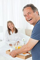 Man bringing breakfast to his wife at home