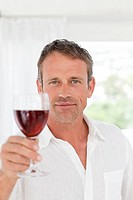 Man with his wineglass in his kitchen at home