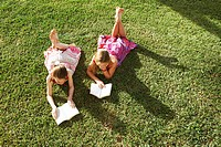 Girls lying on grass reading books