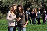 Two teenage girls with mobile phone at field, his friends are at the background