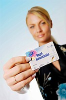 Young woman holding insurance card, Kopfpauschale, capitation fee, written on it
