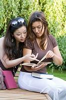 Female friends reading a book